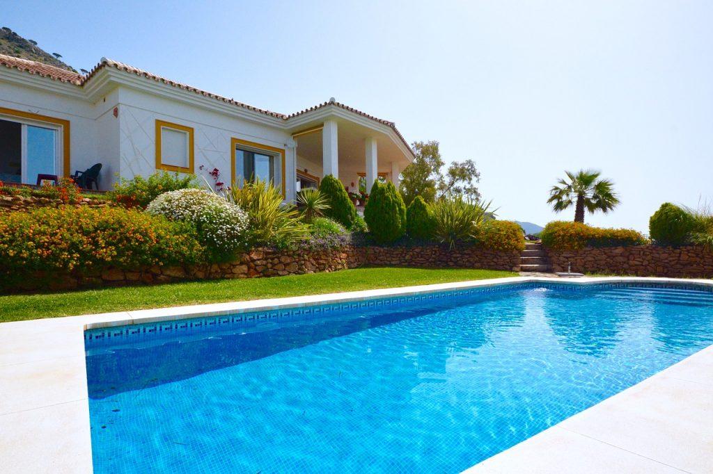 extérieur de maison avec piscine et massifs végétaux près d'un muret en pierres