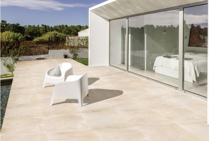 terrasse en carrelage avec deux chaises design devant baie vitrée