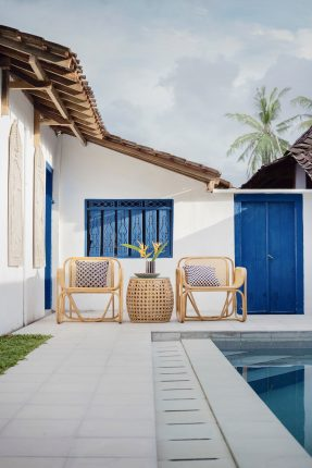 terrasse blanche avec piscine et mobilier extérieur en rotin