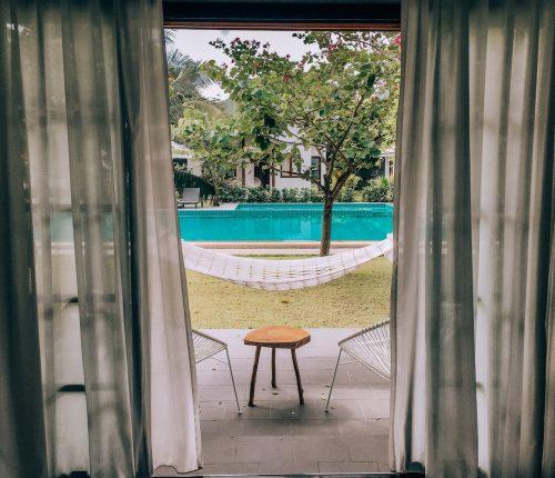fenêtre ouverte sur un jardin avec piscine